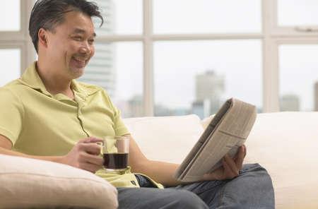davenport: Asian man with coffee and newspaper on sofa