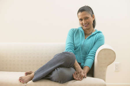 casualness: Woman sitting on sofa and smiling