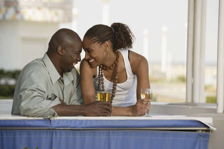 mid life: African couple smiling at each other with cocktails