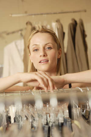 Woman leaning on rack at clothing store