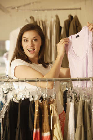 Woman holding up shirt at clothing store