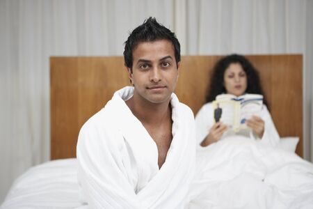 middle eastern: Middle Eastern man in bathrobe with woman reading in bed