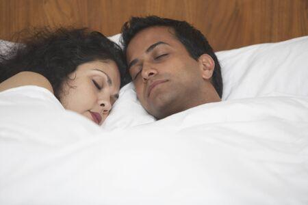 pareja durmiendo: Medio dormido par de Oriente en la cama LANG_EVOIMAGES