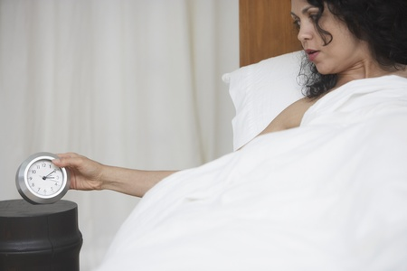 bedcover: Woman looking at alarm clock from bed LANG_EVOIMAGES