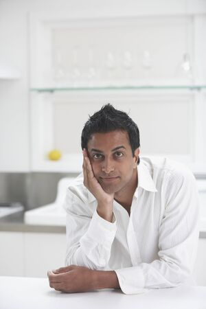 rousing: Middle Eastern man leaning on counter in kitchen