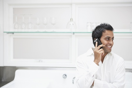 Middle Eastern man using cell phone in kitchen