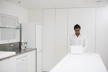 easygoing: Man using laptop on counter in kitchen