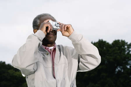 motioning: Senior African man talking photograph outdoors LANG_EVOIMAGES