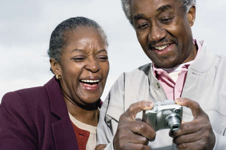 mid life: Senior African couple smiling and looking at digital camera