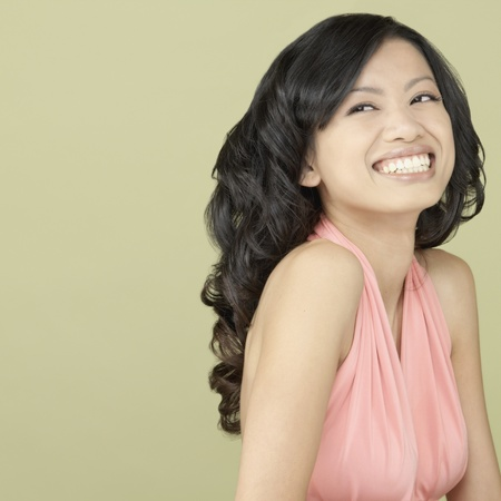 facing away: Studio shot of Asian woman laughing LANG_EVOIMAGES