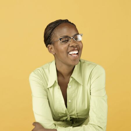 mischievious: Studio shot of African woman wearing eyeglasses and smiling