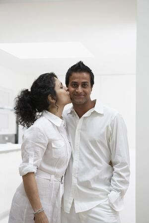 adoring: Middle Eastern couple hugging with woman kissing mans cheek LANG_EVOIMAGES