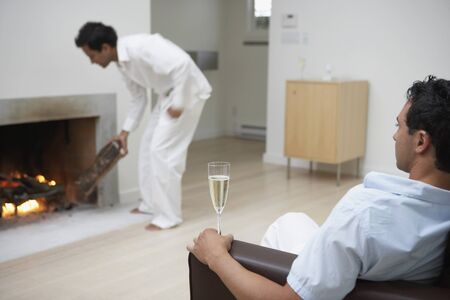easygoing: Man on sofa with champagne while male friend puts wood in fireplace