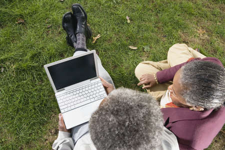 finding a mate: Senior African couple using laptop on grass outdoors LANG_EVOIMAGES