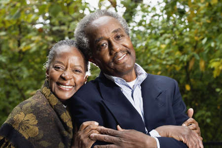 buddies: Senior African couple smiling in woods LANG_EVOIMAGES