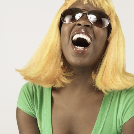 plugging: Studio shot of African woman wearing blonde wig and sunglasses