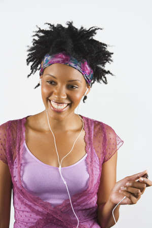 Studio shot of African woman using mp.3 player Stock Photo
