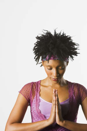 African woman with eyes closed and palms together in front of heart Stock Photo