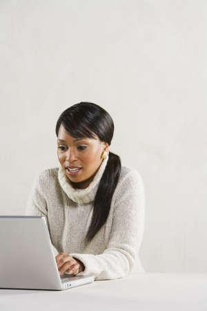 daydreamer: Studio shot of African woman using laptop