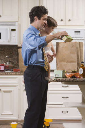 Dad after Work with Toddler and Groceries Stock Photo