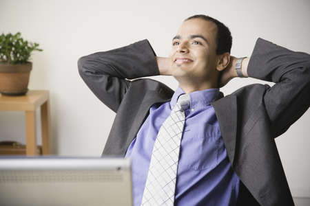 tired businessman: Indian businessman smiling with hands behind head