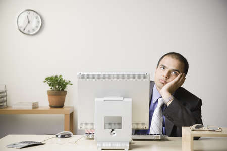 Indian businessman leaning head on hand at desk