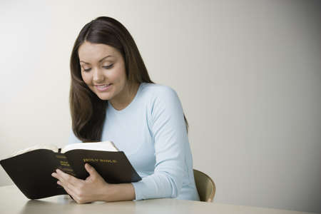 holding the head: Hispanic woman reading bible LANG_EVOIMAGES