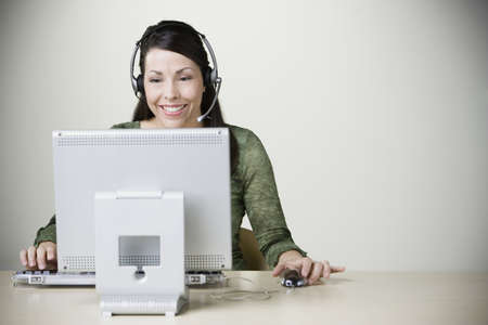 casualness: Hispanic businesswoman with headset working on computer