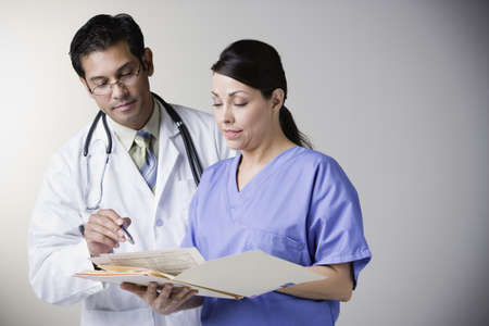 general knowledge: Hispanic male doctor and nurse reading file