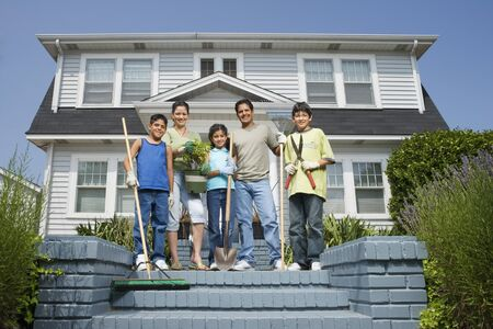 bambino: Hispanic family with gardening tools in front of house LANG_EVOIMAGES