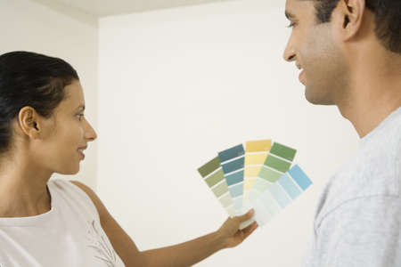 casualness: Indian couple looking at paint swatches