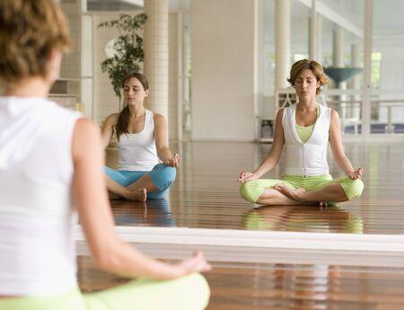 exerting: Two Hispanic women meditating at health club
