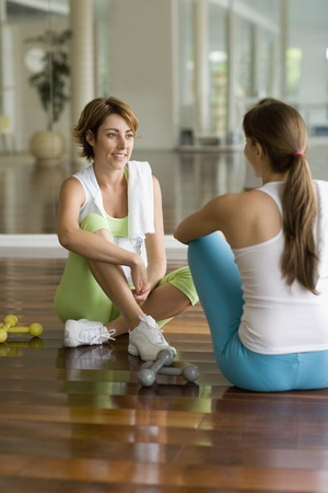 exerting: Two Hispanic women talking in health club