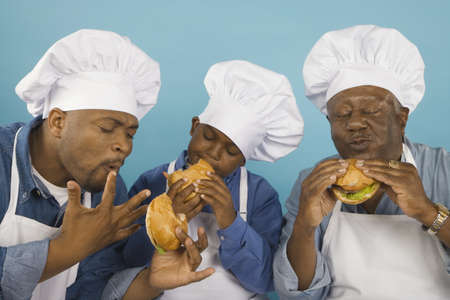 africanamerican: Multi-generational African male family members in chef's hats eating hamburgers LANG_EVOIMAGES