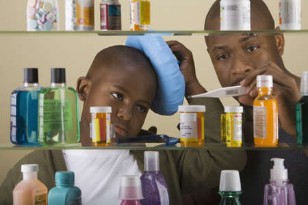 fathering: African father taking son's temperature in front of medicine cabinet