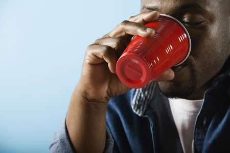 grampa: African man drinking from plastic cup