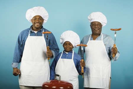 thirties portrait: Multi-generational African male family members with barbeque grill