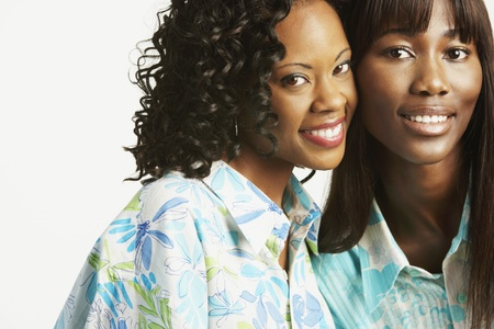 african american woman silhouette: Studio shot of two African women smiling