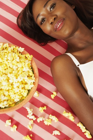 African woman laying next to popcorn bowl