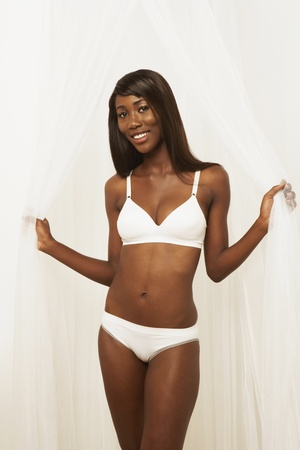 seminude: Semi-nude African woman standing in parted curtains LANG_EVOIMAGES