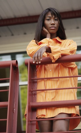 casualness: Low angle view of African woman on balcony LANG_EVOIMAGES