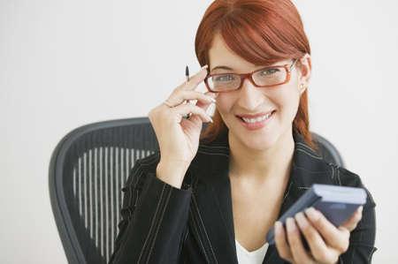 typist: Hispanic businesswoman holding electronic organizer LANG_EVOIMAGES