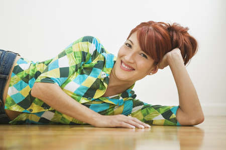 Hispanic woman laying on floor Stock Photo