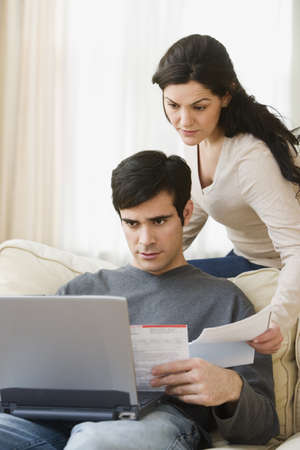 triumphing: Hispanic couple paying bills online with laptop LANG_EVOIMAGES