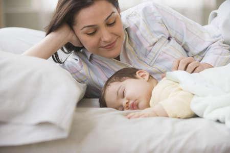 lovemaking: Hispanic mother smiling at sleeping baby LANG_EVOIMAGES