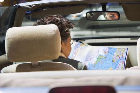 acknowledging: Senior Hispanic woman looking at map in car LANG_EVOIMAGES