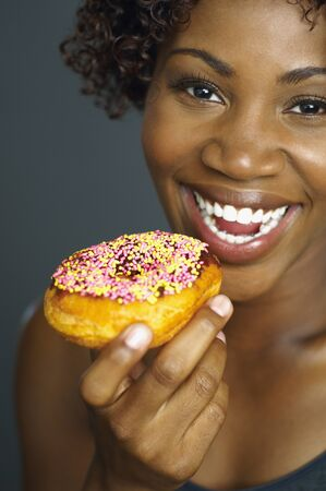 munching: Close up of African woman eating doughnut