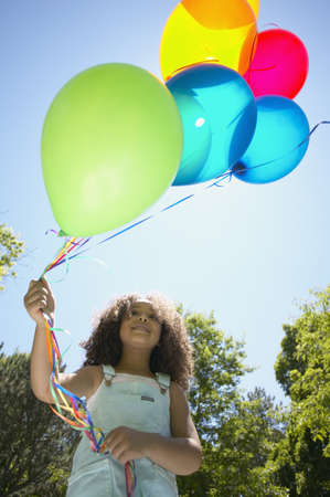 casualness: Low angle view of African girl holding balloons