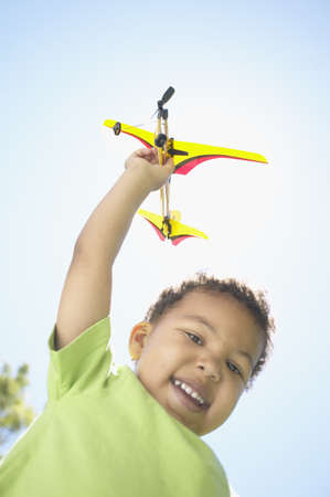 jamaican ethnicity: African boy playing with toy airplane