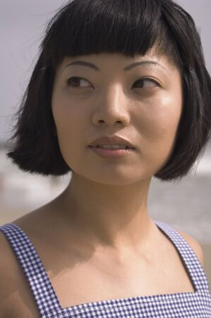 adventuresome: Close up of Asian woman at beach LANG_EVOIMAGES